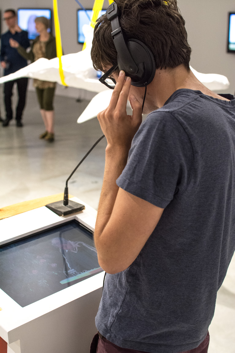 Listening to Nathaniel Wong's 'Thus Spoke Death and Transfiguration' at Lossless, SFU MFA Graduating Exhibition at Audain Gallery, 2014. Photo by Ash Tanasiychuk for VANDOCUMENT